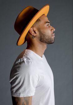 Zion wears hat Magill Fedora and t-shirt Frame Denim.