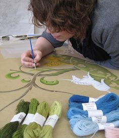 The artist is making sure that the four shades of green and the four shades of blue are each clearly easily distinguishable so the needlepoint rug embroiderer can follow the pattern without making errors. Image courtesy The Royal School of Needlework, London.