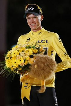 Christopher Froome with the spoils of victory on the podium in Paris after the 100th Tour de France