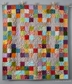 Colourful simple baby quilt with subtle grey crosses interspersed. By Audrie at Blue is Bleu blog.