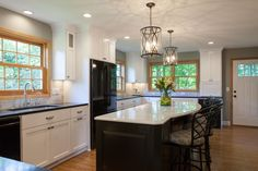 Black granite countertops and black appliances provide contrast against the white perimeter cabinets in this transitional kitchen. Roles are reversed for the kitchen island, which features white quartz countertops and a dark base.