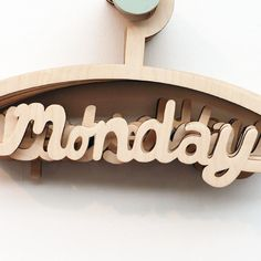 "Wooden coat hanger with the lower cross bar shaped like the word ""monday"""