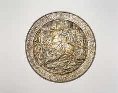 Shield Depicting Saint George Slaying the Dragon Date: ca. 1560–70 Geography: Milan Culture: Italian, Milan Medium: Steel, gold, silver Dimensions: Diam. 23 1/4 in. (59.1 cm); D. at center 3 1/16 in. (7.8 cm); Wt. 8 lb. 6 oz. (3810 g) Classification: Shields Credit Line: Gift of William H. Riggs, 1913 Accession Number: 14.25.1884