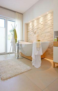 freistehende badewanne und steinwand - moderne bäder gestalten