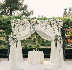 27 Neutral Wedding Ideas for Nuptials in Any Season White drapery wedding ceremony structure chuppah ivory flowers greenery white stage grass lawn. Wedding Altars, Wedding Venue Decorations, Wedding Ceremony Decorations, Wedding Ideas, Wedding Ceremonies, Wedding Backdrops, Wedding Themes, Wedding Designs, Wedding Stuff