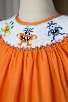 This is a beautiful dress that is ready for your smocking design, aka ready to smock dress. The bishop style is made in 100% orange cotton and the pleated insert around the collar is white, baby sizes