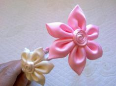 Diadema forrada de raso, adornada con dos flores a contraste de tela de 7 y 4 cm.