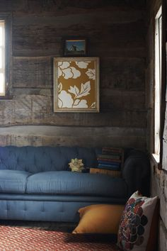 Anthropologie framed wallpaper swatch on a fabulous log cabin wall.