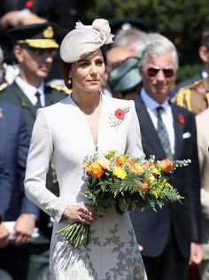 Kate Middleton Photos Photos - Catherine, Duchess of Cambridge with flowers during a ceremony at the Commonwealth War Graves Commisions's Tyne Cot Cemetery on July 31, 2017 in Ypres, Belgium. The commemorations mark the centenary of Passchendaele - The Third Battle of Ypres. - Members Of The Royal Family Attend The Passchendaele Commemorations In Belgium