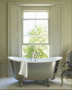 decadent, chrome (!!) bathtub highlighted by a beautiful floor-length window