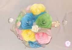 Bouquet is made from coffee filter paper and is shown in different shades of pink, blue, yellow and green with coordinating pearl sprays, tiny foam Roses with ivory, blue and pink tulle mixed into and surrounding the flowers. The handle is wrapped in ivory satin ribbon and delicate ivory bows.