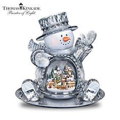 Deck the Halls.   Thomas Kinkade Lighted Musical Crystal Sledding Snowman.Limited-edition crystal snowman sculpture holds an illuminated sculptural Thomas Kinkade village scene inside. Plays holiday medley.