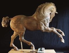 """""""Walnut horse with lifted legs"""" by Lina Binkele. Wood carving, 60"""" x 78,5"""" x 21"""". Brings to mind marble statues and carousel horses: an interesting intersection."""