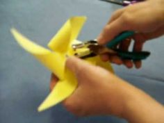 how to make a one minute pinwheel with sissors, paper, hole puncher, pencil, glue, pipe cleaner