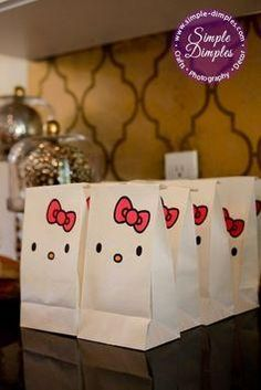 DIY white paper lunch bags to create Hello Kitty goodie bags. Get more inspiration for an adorable Hello Kitty themed party from @heatherterrell.