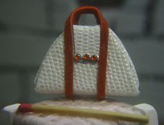 Handmade miniature handbag. Textured white leather with red trim and diamantes.