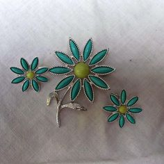A vintage Sarah Coventry, flower brooch/pin and clip-on earring set.  Faux turquoise plastic set into silver tone metal for the petals and a lemon