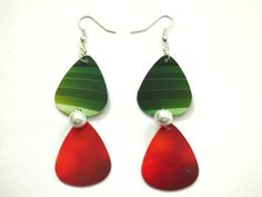 Surprise your music-lover with these beautiful guitar pick and pearl earrings! Red, green and white for the Christmas season, these earrings are the perfect gift for the musician in your life, the guitar player who has a sleek sense of style or yourself if you are looking for a musically inclined treat.  Each of these pairs of red and green guitar pick earrings features a glass pearl accent. Your pair of dual guitar earrings measures approximately three inches. Each pair of these earrings…