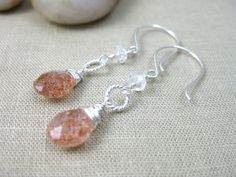 Sun and Moon Earrings | Twinkling sunstone briolettes sparkle delightfully and are paired with cool glowing moonstone rondelles. The gems sandwich twisted sterling silver rings and dance beneath my hand forged earwires, also in sterling silver. The sunstone exhibits a bevy of orange flecks and even some opal-like blue flashes.