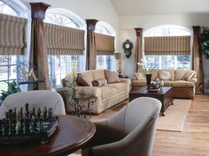 The elegance of this living room is beautifully extended to the windows with silk Roman shades adorned with glass beading. Design by Phyllis Harbinger.