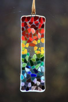 This unique hand made fused glass sun catcher is a colourful way to brighten up a window. The small pieces of transparent and opal colours have been arranged to create a rainbow effect and look great with the sun shining through.  All my items are made from hand cut glass, assembled and fired in my kiln at home. This sun catcher is made of individually cut pieces of transparent and opal glass in rainbow colours. These have been placed onto a clear glass base and fully fused to create a…