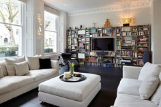 woodwork and molding, dark floors, light upholstery, wall of books, Le Corbusier lounge chair