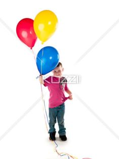boy keeps cool while holding balloons - Little boy looks uncertain holding the balloons but keeps cool and smiles for the camera.