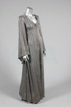 A Biba silver and black 'glam rock' knitted lurex evening gown, late 1960s.     One of my mom's full length gowns from this time period is made of this very same fabric.  Hers is more of a fitted bit with an Egyptian-collar looking band of darker fabric at the top, w/fitted long sleeves.  Haven't worn it in a few years but must unpack and post!