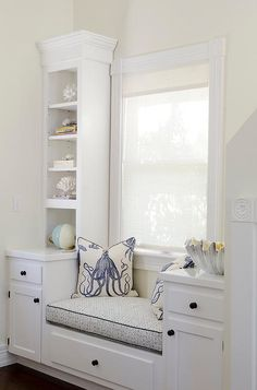 Cottage home office features a built-in window seat lined with white and blue octopus pillows flanked by tall shelves atop cabinets.