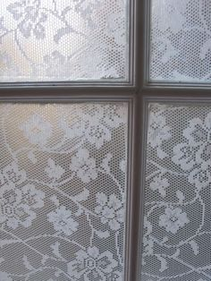 Make a cornflour podge (aabout 2 tablespoons cornflour mixed with about an equal amount of cold water. Add to about a cup and a half of boiling water from the kettle. Use the resulting jelly to paint a thick layer onto the window pane. Cut out a rectangle of ironed lace using a template. Paste onto the pane, and cover with another layer of podge. Leave to dry. Wash with warm water to remove.