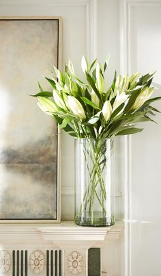 A simple glass cylinder with long stem lilies.