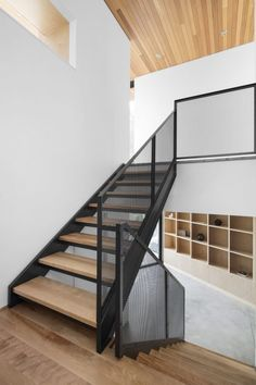 A steel and wood staircase leads to the second floor of this house, where the design team placed an open-plan kitchen, dining room and living room, along with the master suite.