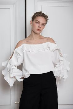 The Calin Top in White featuring thin straps, square neckline, dimple sleeves in ruffle detailing with self-tie. Pull on.