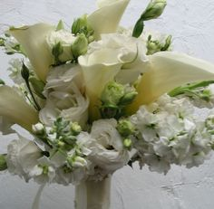 A bridal bouquet consisting of white calla lilies and white stock. See our entire selection at www.starflor.com.  To purchase any of our floral selections, as gifts or décor, please call us at 800.520.8999 or visit our e-commerce portal at www.Starbrightnyc.com. This composition of flowers is generally available for same day delivery in New York City (NYC).  WB056