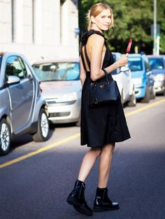 A backless black dress is worn with combat boots and a small Prada satchel bag