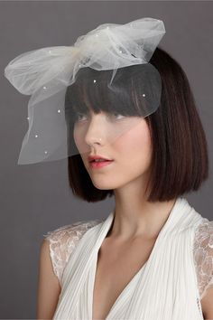 """Weightless Birdcage Veil     Voluminous and sprinkled with hand-beaded pearls, a bounteous bow is settled above a fine mist of tulle that floats away from your face, leaving your lips free to bestow your first marital kiss. From Kristi Bonnici. 9""""L, 9""""W. Nylon bridal tulle, plastic pearl beads, plastic hair comb, satin ribbons. Handmade in Australia."""