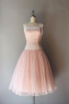 Prachtige jaren 1950 bleke roze partij jurk met Tule verrekening overlay met kleine bosjes itty bitty bogen maken! De jurk heeft een vierkante hals met wit kant trim en riemen. De lace siert ook de daling van de taille. De natuurlijke taille is verminderd en de rok is erg vol en schuimig. Het heeft drie volledige lagen, de roze taffeta voering, een Tule-tussenlaag en de netto-overlay. De jurk sluit met een metalen rits van kant.  ◊ voorwaarde: geweldig! Er zijn enkele kleine, zeer zwakke…