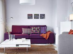Sala com sofá de três lugares com capa em vermelho-roxo e mesa de centro em branco com pernas de aço cromado
