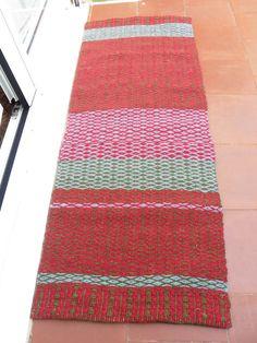 Se trata de una alfombra hecha con lanas 100% naturales en un telar de bajo lizo. Estos trabajos los realizamos en un taller escuela que hay en Barcelona, en el que aprendemos y experimentamos con los telares y las lanas. La alfombra combina los colores granate, verde y un gris azulado. Hemos combinado los colores de muchas maneras para hacer le trabajo más original y único. Es muy práctica para una terraza o para el interior de la casa sobretodo si se trata de una casa de campo. Medidas…