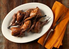 A recipe for barbecued quail with Arizona sauce, a Southwestern style BBQ sauce made with tequila, mesquite honey, wild chiltepin chiles and stock.