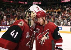GLENDALE, AZ - DECEMBER 10: Goalie Mike Smith #41 and Jamie McGinn #88 of the Arizona Coyotes bump helmets in celebration of a 4-1 victory against the Nashville Predators at Gila River Arena on December 10, 2016 in Glendale, Arizona. (Photo by Norm Hall/NHLI via Getty Images)