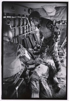 [Helicopter crew chief James C. Farley (R) checking on a wounded crewmate while wounded pilot, Lt. James E. Magel, lies dying at his feet]