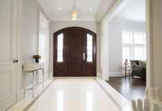 This foyer sets the mood for the whole house. Its chic and modern but the warm stained wood on the front door grounds the space. www.cmidesign.ca #CMID