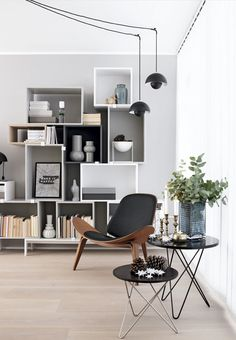 Bookshelves, chair, and tables. Greys black and white.
