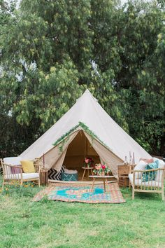 Create a bohemian lounge tent with some wooden chairs and woven rugs.