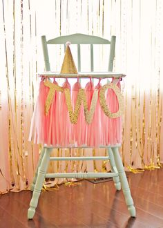 We love this decorated high chair for a smash cake! The gold glitter banner + tissue tassels looks fab.
