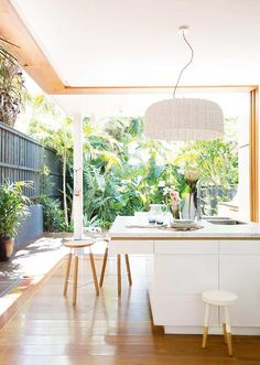 Dining space with a sliding NanaWall, wood floors, white walls, white light fixture, white tabletop, and white barstools