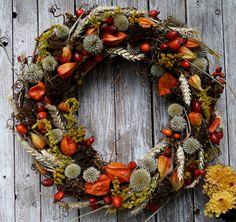 Wianek jesienny. Eko-styl. Materiały: podstawa z gałązek winorośli, owoce dzikiej róży, physalis, echinops, tanacetum, solidago, kłosy zbóża. Średnica ok. 45 cm.