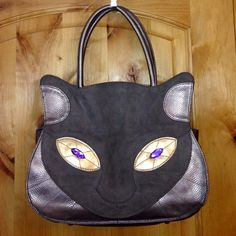 IRREGULAR CHOICE Pewter KITTY CAT Bag Purse EUC IRREGULAR CHOICE Pewter Violet Eyes KITTY CAT Tote Bag Purse; Luxurious Velvety Turquoise Interior & Magnetic Closure! EUC    I bought this to match my boots but never used it. I'd love to find this unique gorgeous bag a new home because it deserves to be seen!   •MEASUREMENTS: will be added shortly  •MATERIAL: will be added shortly  *My Home is Smoke-Free & Pet-Free!* Irregular Choice Bags