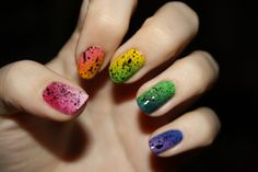 Using a sponge or a stippling brush, use various colors in the spectrum of the rainbow and then go over it with black more sparsely for the splatter effect.